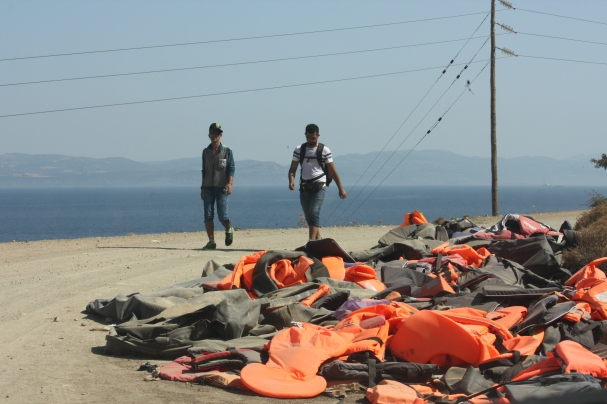 Refugees walk past discarded lifejackets on the road from Eftalou to Mytilini